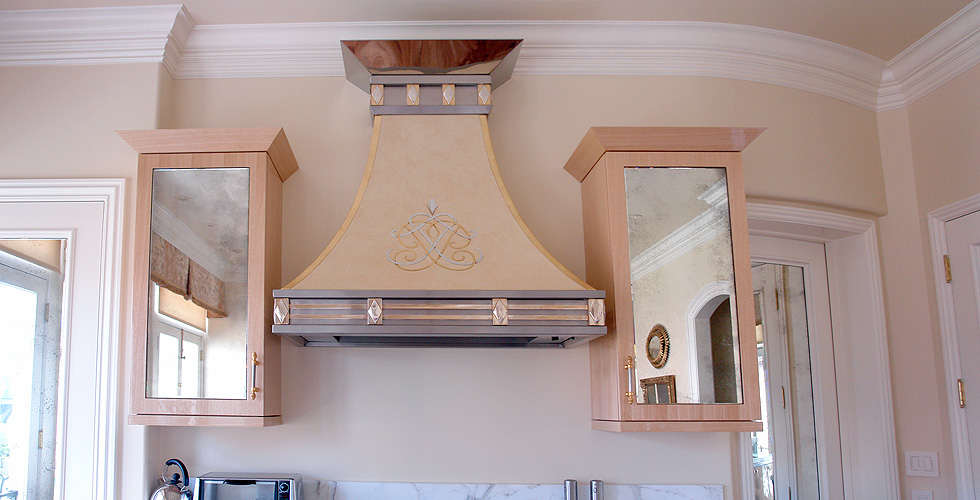 Kitchen hood topped with mirrored stainless steel, faux-painted and softened with glossy taywood cabinetry surrounding