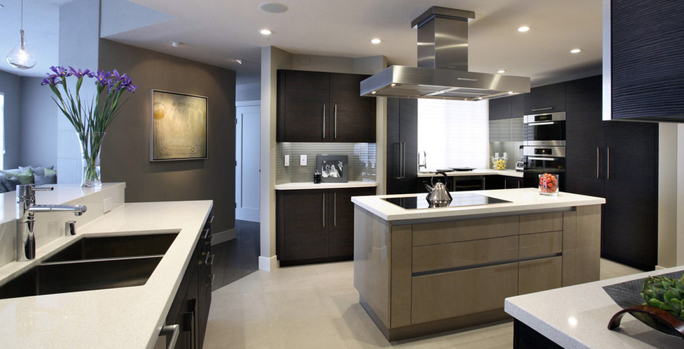 The kitchen features bold stainless steel handles, further emphasizing the kitchen's clean, sleek lines