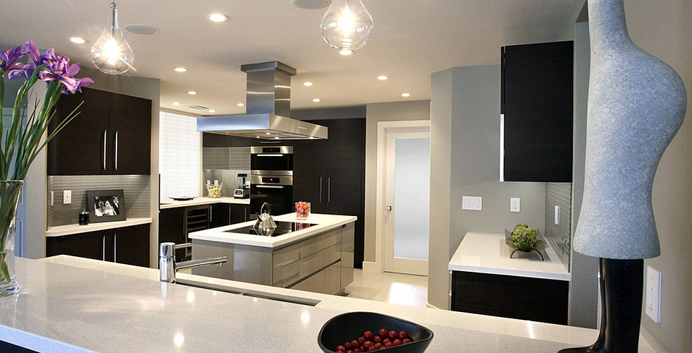Opposite the island the kitchen cabinets are figured quarter-sawn sycamore in a silver mink high gloss finish.
